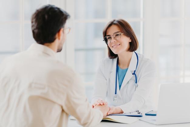 Médica confiante segura as mãos de pacientes doentes e convence que tudo ficará bem Foto Premium