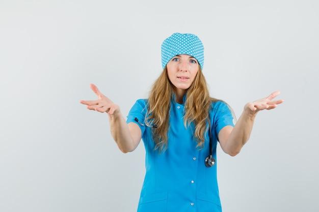 Médica de mãos dadas recebendo algo em uniforme azul Foto gratuita