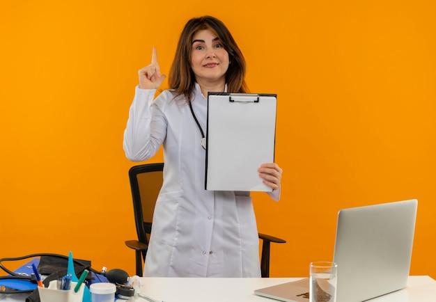 Médica de meia-idade satisfeita vestindo túnica médica com estetoscópio sentada na mesa de trabalho no laptop com ferramentas médicas segurando a prancheta e aponta para cima na parede laranja com espaço de cópia Foto gratuita