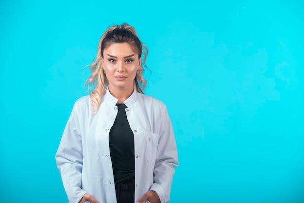 Médica de uniforme branco em postura profissional. Foto gratuita