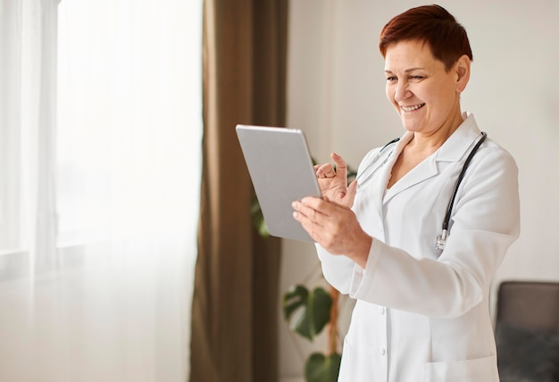Médica do centro de recuperação cobiçoso, sorridente, idosa, com tablet e estetoscópio Foto gratuita