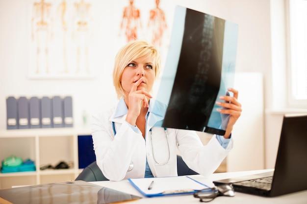 Médica estudando radiografia de coluna Foto gratuita