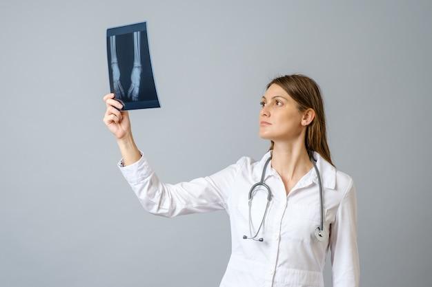 Médica examinando a imagem de raio-x das pernas de um bebê recém-nascido. isolado sobre parede cinza Foto Premium