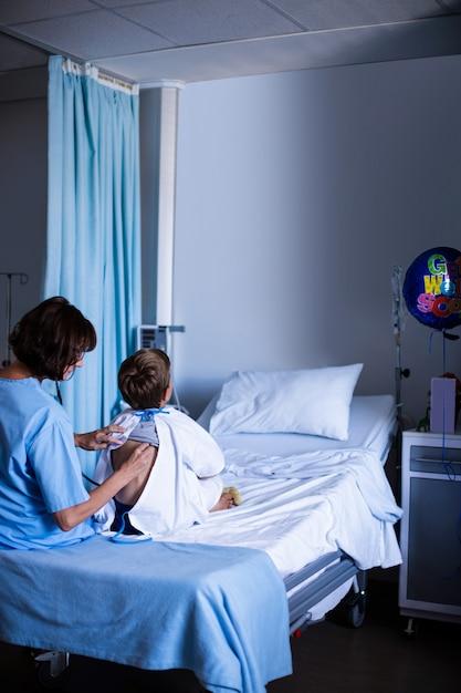Médica examinando paciente com estetoscópio Foto Premium
