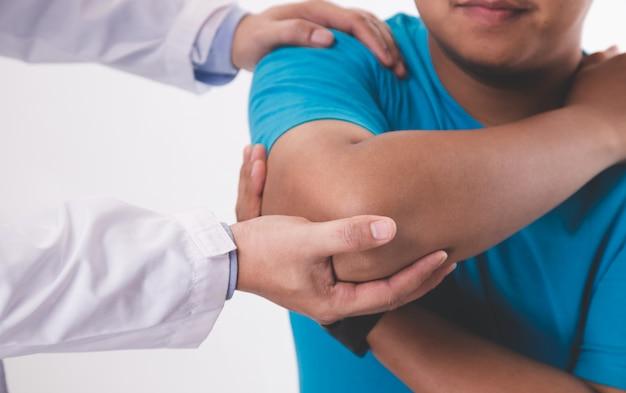 Médica, fazendo massagem no pescoço para paciente do sexo masculino. Foto Premium