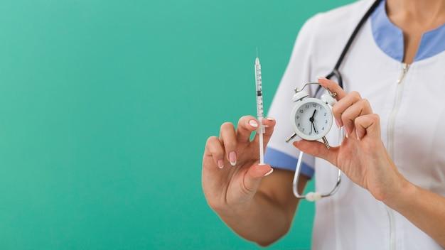 Médica mãos segurando uma seringa e um relógio Foto gratuita