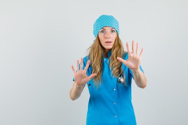 Médica mostrando as palmas das mãos de forma preventiva em uniforme azul e parecendo assustada. Foto gratuita