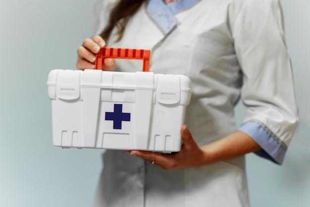 Médica, segurando a caixa de primeiros socorros no hospital Foto Premium