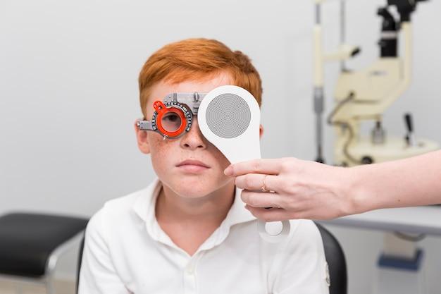Médica, verificando a visão do garoto sardento com quadro de julgamento optometrista na clínica Foto gratuita