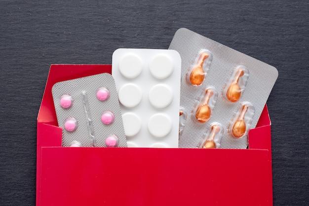 Medicamento farmacêutico e suplemento com cápsulas e comprimidos em embalagem. tratamento médico que ajuda a atividade, apoio à saúde e sistema imunológico. recebendo um pedido da internet em um envelope. Foto Premium