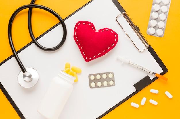 Medicina caindo da garrafa sobre a área de transferência; estetoscópio; forma de coração costurada; injeção; remédio embalado em blister contra mesa amarela Foto gratuita