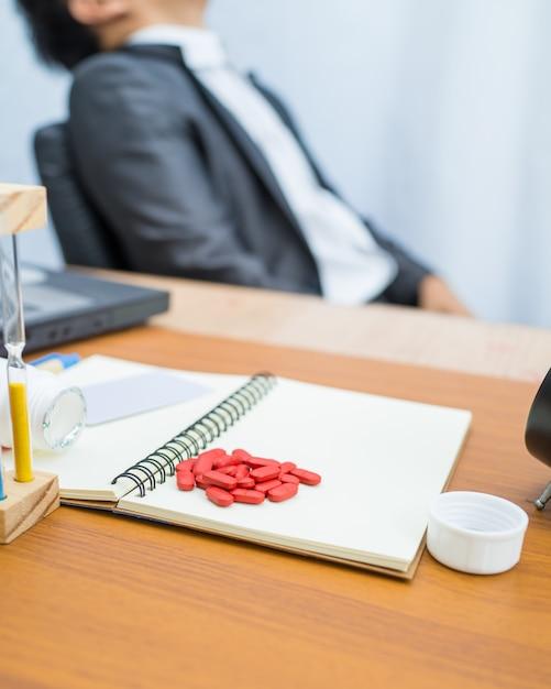 Medicina vermelha no caderno com tabela de madeira padrão na cadeira de homem de negócios turva, Foto Premium