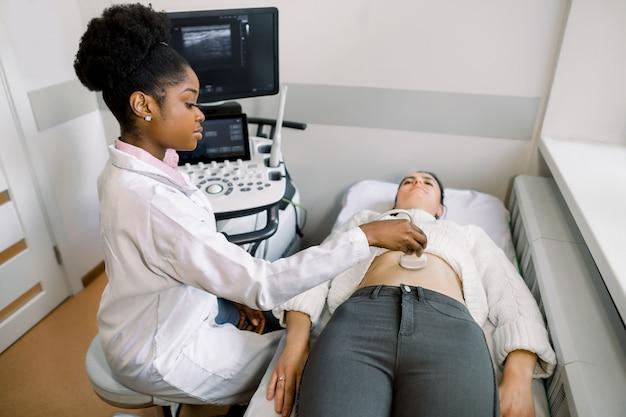 Médico africano jovem movendo o transdutor de ultrassom na barriga da mulher no hospital Foto Premium