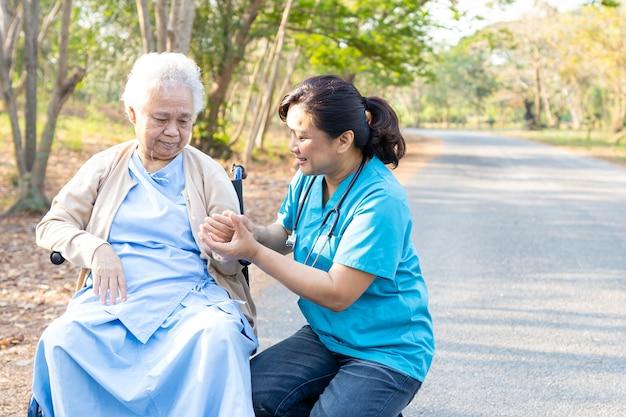 Médico, ajuda e cuidados paciente asiático sênior mulher sentada na cadeira de rodas no parque. Foto Premium