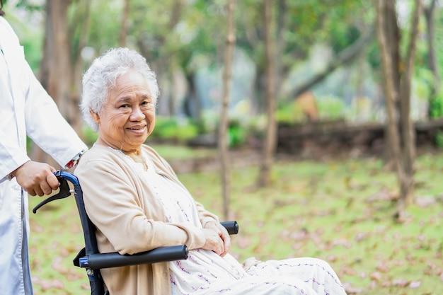 Médico ajuda paciente asiática sênior mulher sentada na cadeira de rodas no parque. Foto Premium