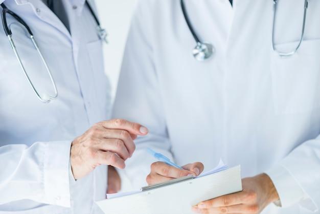 Médico anônimo, ajudando o colega a escrever prescrição Foto gratuita