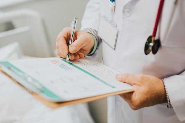 Médico anotando sintomas de um paciente Foto gratuita