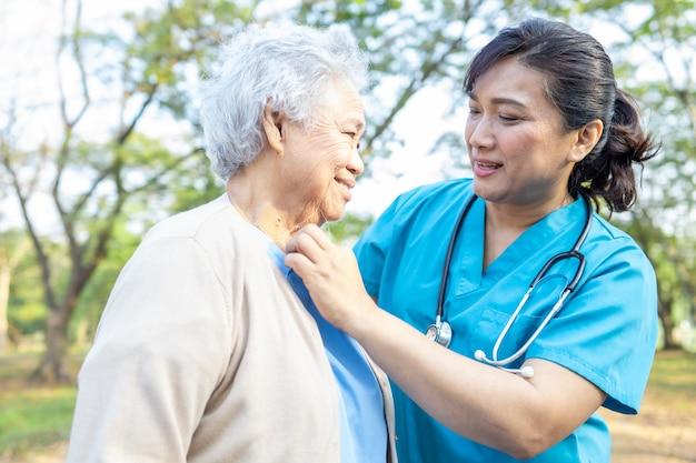 Médico apoio paciente mulher sênior no parque. Foto Premium