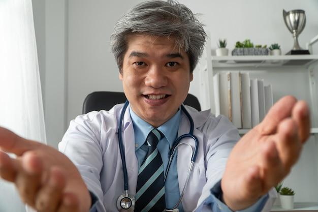 Médico asiático está online visitando um paciente no aplicativo da internet e anota os sintomas Foto Premium
