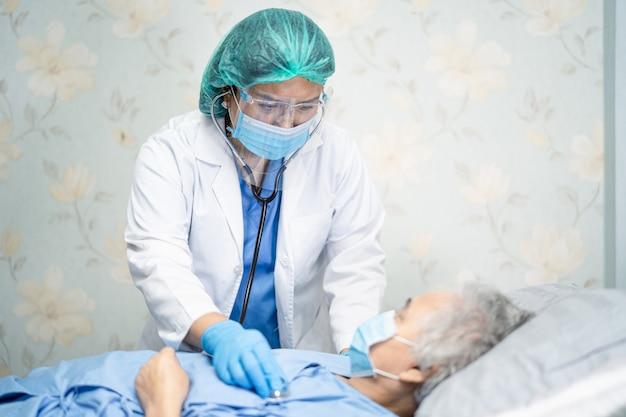 Médico asiático usando máscara facial e epi se adapta ao novo normal para verificar a proteção do paciente covid-19 Foto Premium