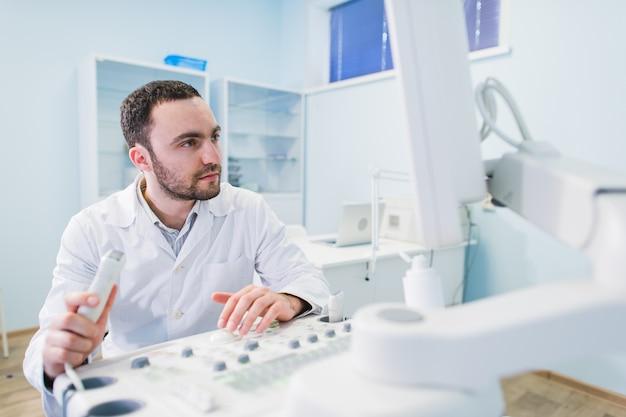 Médico bonito usando uma máquina de ultrassom Foto Premium