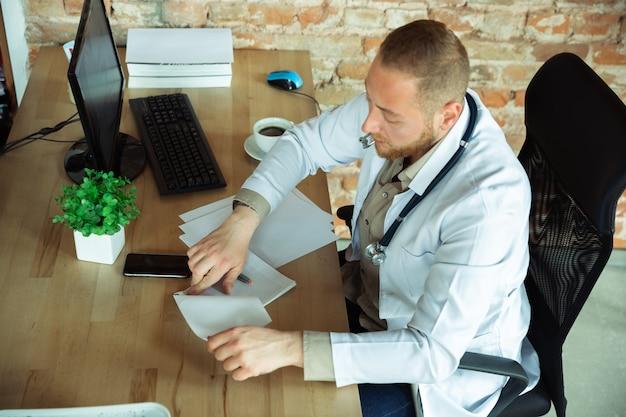 Médico caucasiano consultoria para paciente, trabalhando em gabinete Foto gratuita