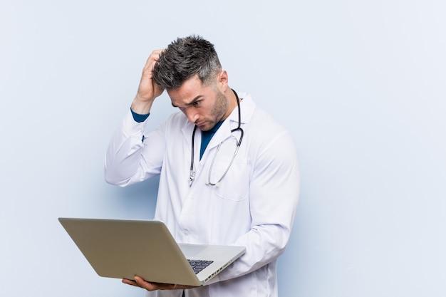 Médico caucasiano homem segurando um laptop sendo chocado, ela se lembrou de uma reunião importante. Foto Premium
