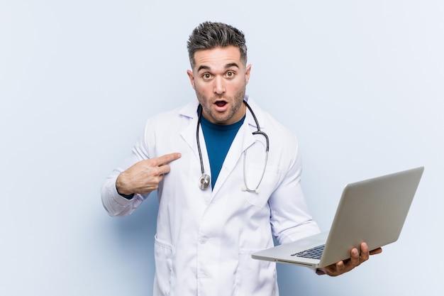 Médico caucasiano homem segurando um laptop surpreendeu apontando para si mesmo, sorrindo amplamente. Foto Premium