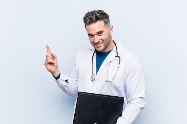 Médico caucasiano homem segurando uma pasta sorrindo alegremente apontando com o dedo indicador fora Foto Premium