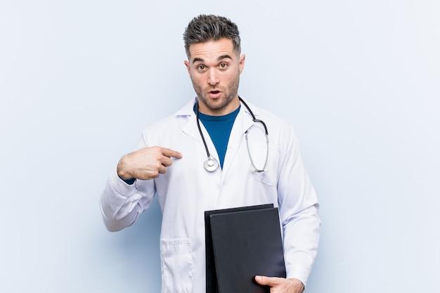 Médico caucasiano homem segurando uma pasta surpreendeu apontando para si mesmo, sorrindo amplamente. Foto Premium