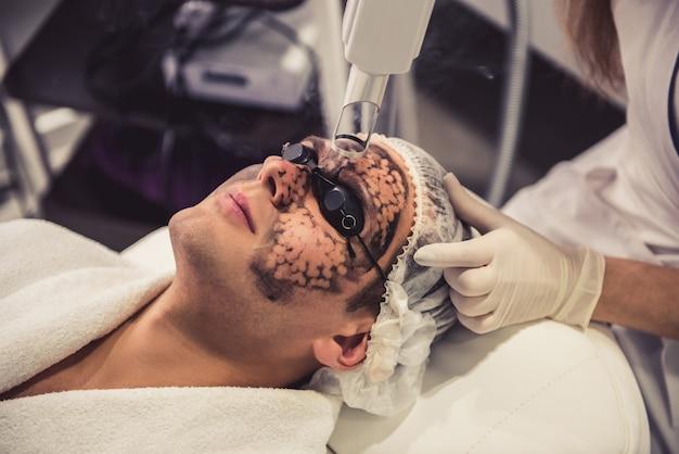 Médico coloca uma máscara preta no rosto. Foto Premium