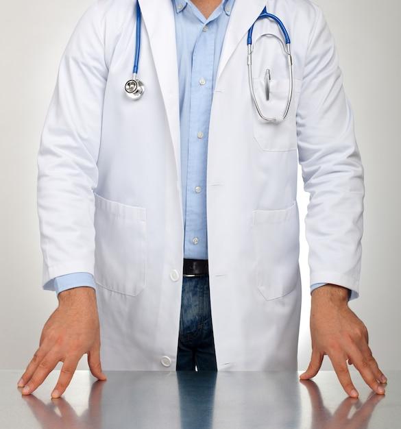 Médico com as mãos descansando em cima da mesa para exame Foto Premium