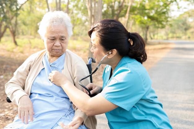 Médico com estetoscópio, verificando a paciente sênior enquanto está sentado na cadeira de rodas no parque. Foto Premium