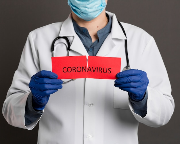 Médico com luvas cirúrgicas segurando papel rasgado escrito coronavírus