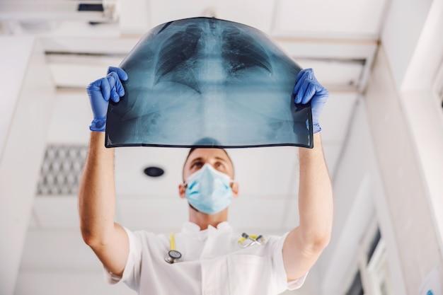 Médico com máscara facial e luvas de borracha, observando um raio-x dos pulmões durante o vírus corona. Foto Premium
