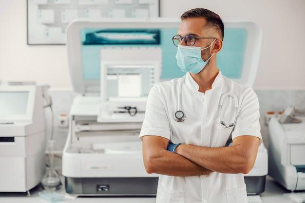 Médico com máscara facial em pé no hospital durante o surto do vírus corona. Foto Premium