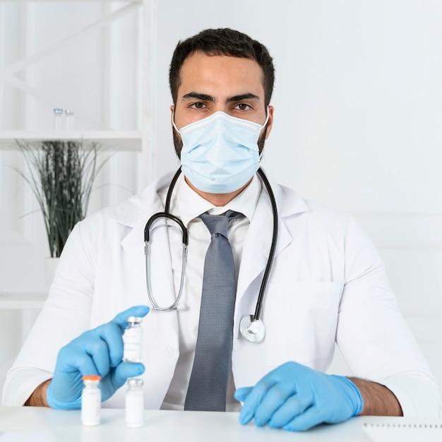 Médico com máscara médica segurando um recipiente de vacina Foto gratuita