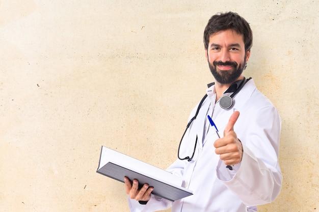 Médico com o polegar acima do fundo branco Foto gratuita