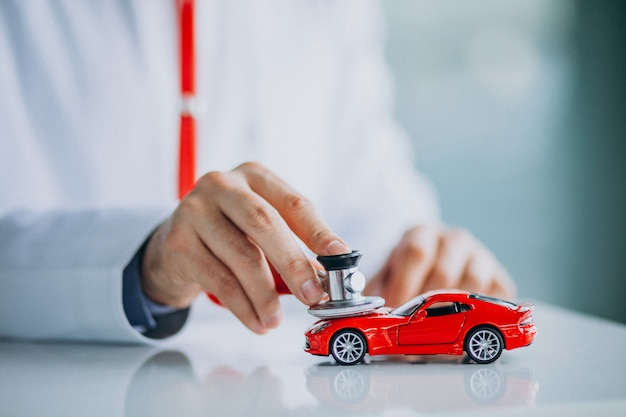 Médico de carro com estetoscópio em uma sala de exposições Foto gratuita
