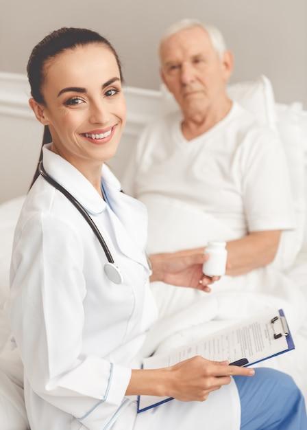 Médico de jaleco branco está segurando um frasco de comprimidos Foto Premium