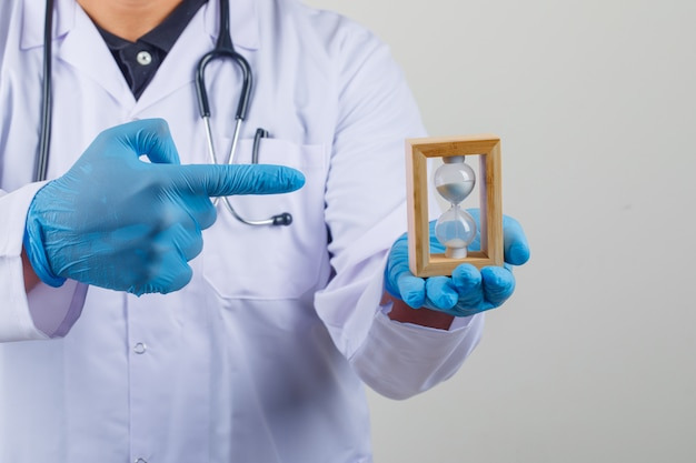 Médico de jaleco branco, mostrando a ampulheta na mão Foto gratuita