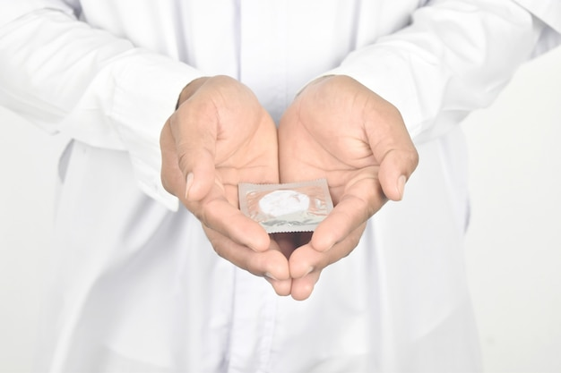 Médico de jaleco branco, segurando o preservativo nas mãos. Foto Premium