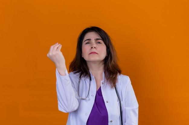 Médico de meia idade vestindo jaleco branco e com estetoscópio, gesticulando com a mão levantada, fazendo o gesto italiano sobre parede laranja isolada Foto gratuita