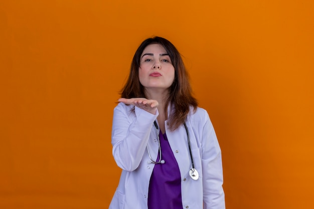Médico de meia idade vestindo jaleco branco e com estetoscópio, olhando para a câmera mandando um beijo com a mão no ar, sendo adorável sobre parede laranja isolada Foto gratuita