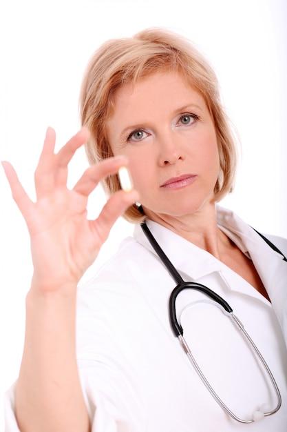 Médico de mulher adulta com comprimidos na mão dela sobre fundo branco Foto gratuita