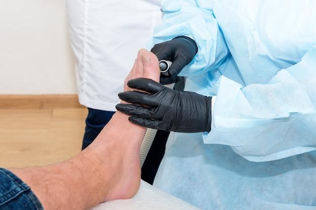 Médico de podologia trata o paciente em clínica moderna Foto Premium