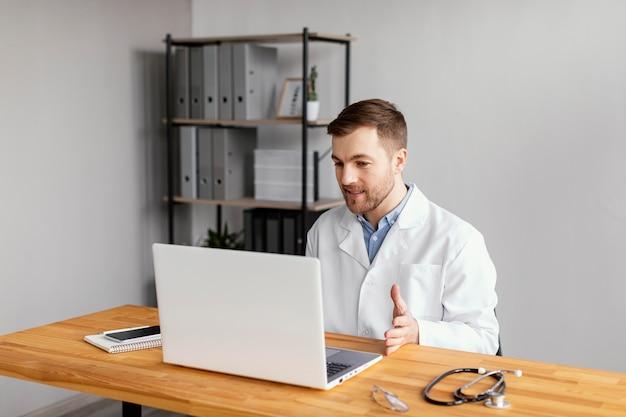 Médico de tiro médio trabalhando na mesa Foto gratuita