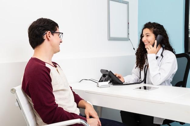 Médico de visão lateral falando no telefone Foto gratuita