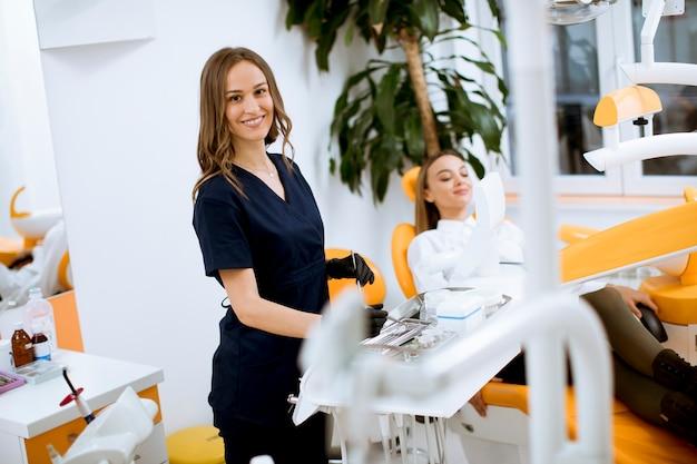 Médico dentista feminino atraente em pé em seu escritório, com uma patinet feminina na cadeira Foto Premium