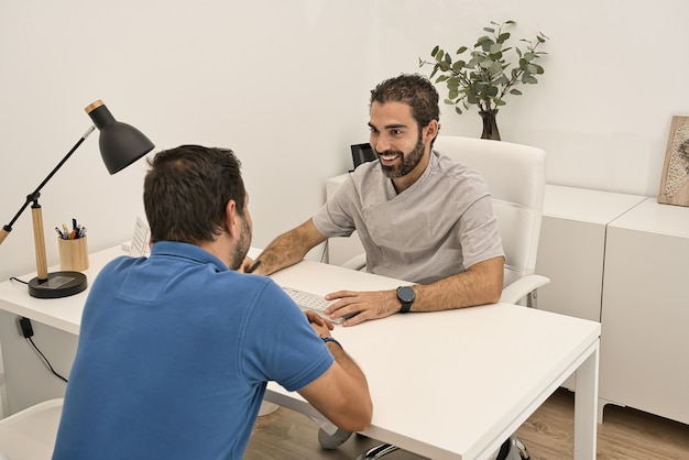 Médico dentista, reunido em seu escritório e sentado em uma mesa, atende com um sorriso a um cliente vestindo uma camisa polo azul em uma clínica odontológica moderna. Foto Premium